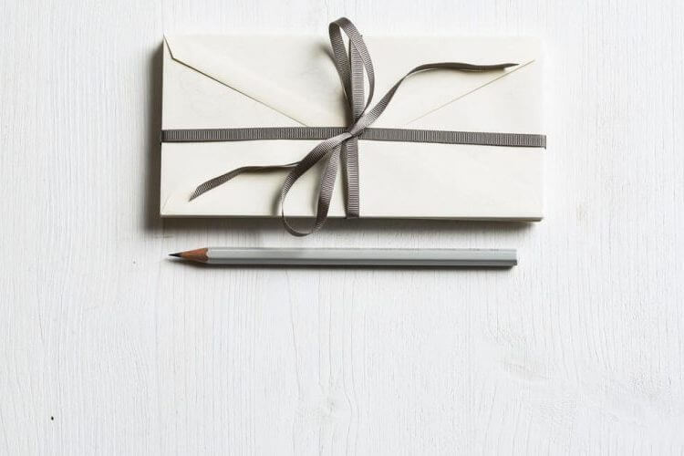 Gift card wrapped and tied with a ribbon and a pencil sitting next to it.