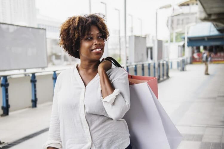 Woman holds a shopping bag after using her point-based customer retail loyalty program