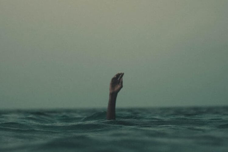 A hand above water symbolizing signs that a company is going under