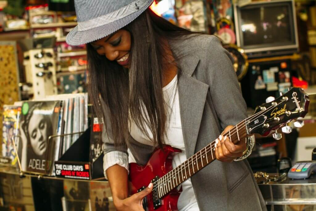 Woman plays new guitar in a music shop