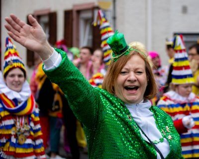 Lady dressed in St. Paddy's Day outfit waving from a parage